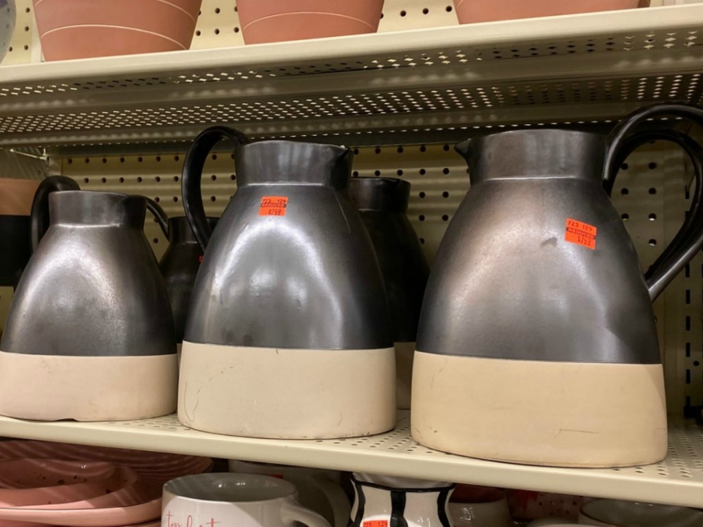 several pitchers on store shelf with orange sale tags