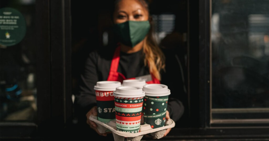 masked barista holding 4 holiday drinks