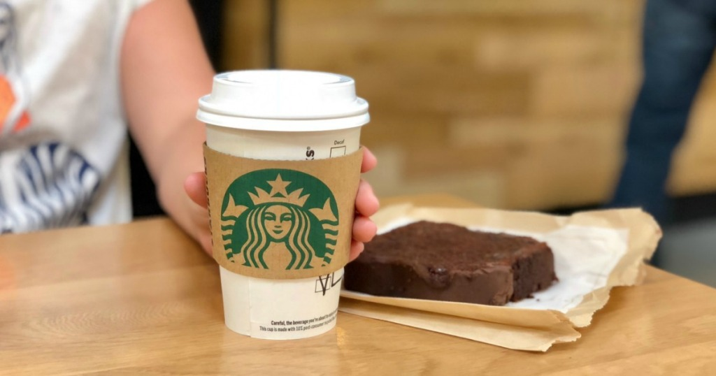 holding Starbucks coffee with chocolate bread in the background