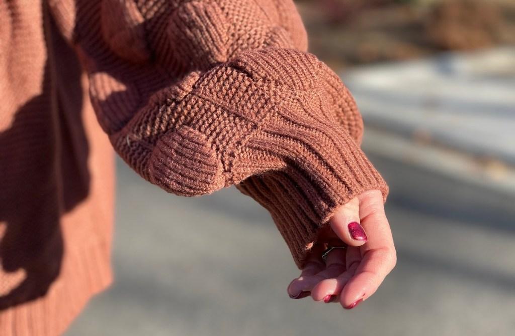 arm wearing pom sleeve sweater outside
