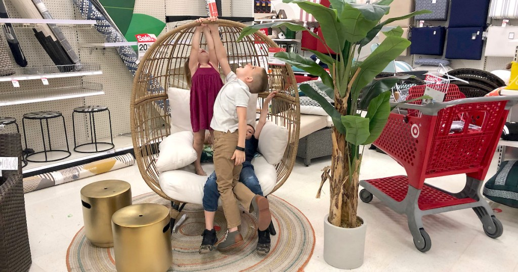 kids hanging from wicker egg chair in target store with red cart in the background