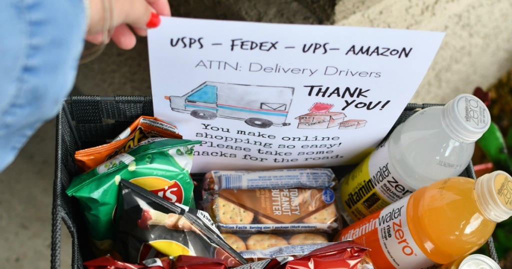 holding thank you delivery driver sign with snacks