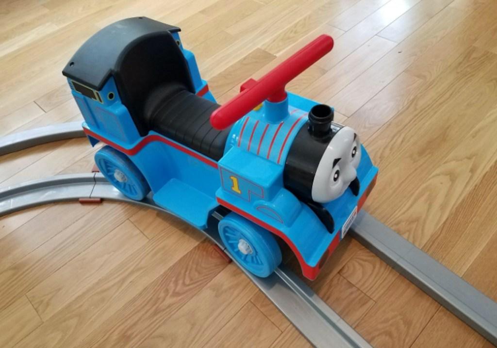 thomas the train toy on tracks on wood floor