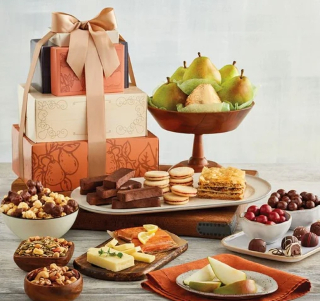 presents stacked in a pile with cheese nuts fruit and various foods