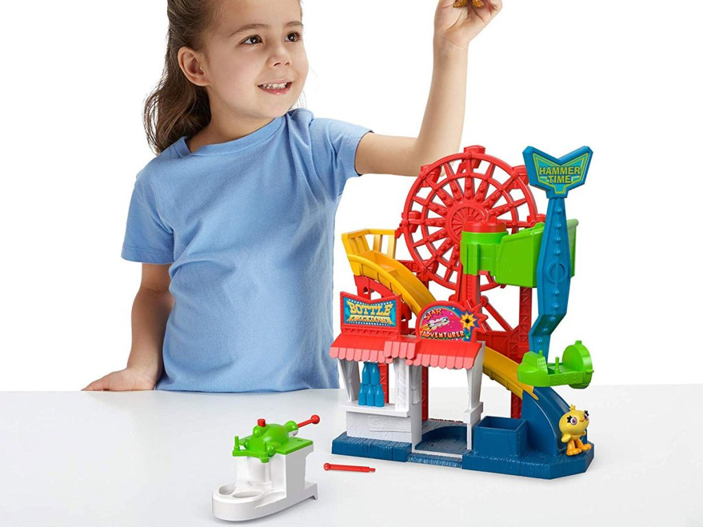 girl playing with Fisher-Price Imaginext Disney Pixar Toy Story 4 Carnival Playset