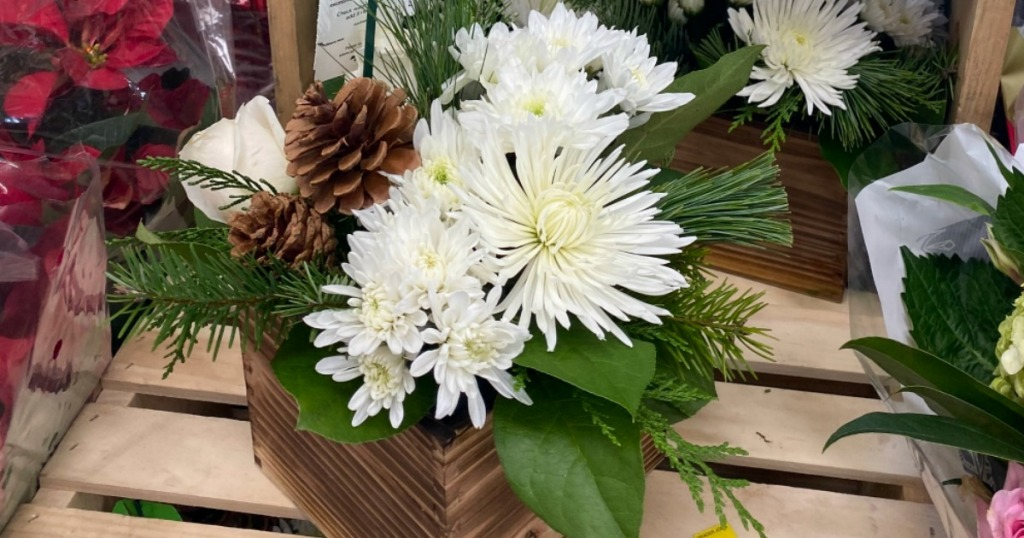 white flowers and pinecones in boxed arrangements