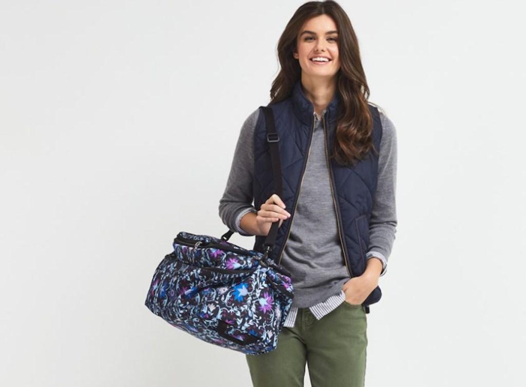 woman smiling holding floral vera bradley travel bag