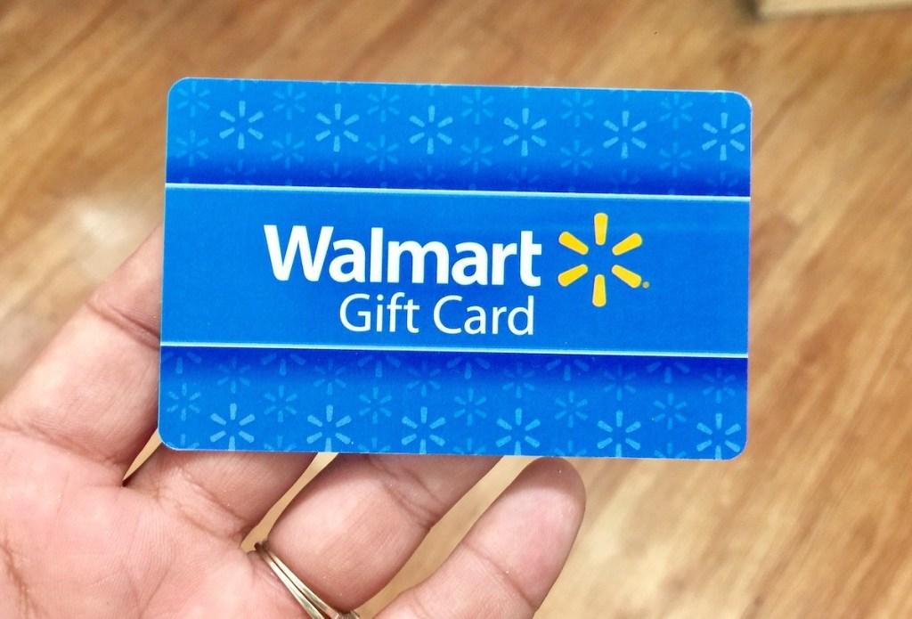 hand holding a blue walmart gift card
