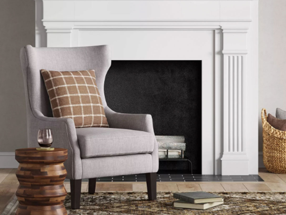Threshold Earnest Lounge Chair Gray by a fireplace