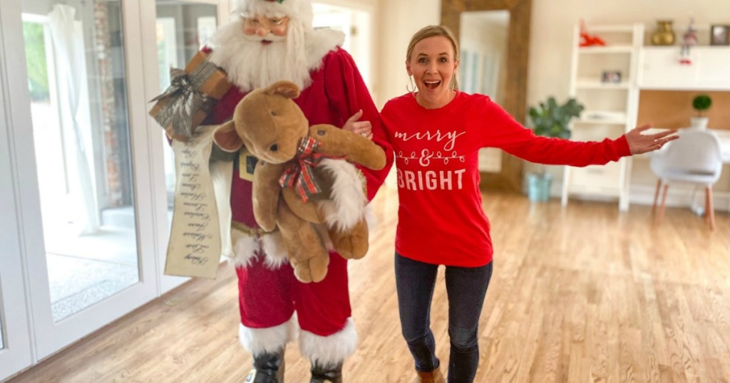 Woman standing next to santa with Christmas shirt