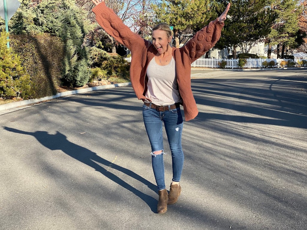 woman with arms in the air wearing cardigans, jeans and boots