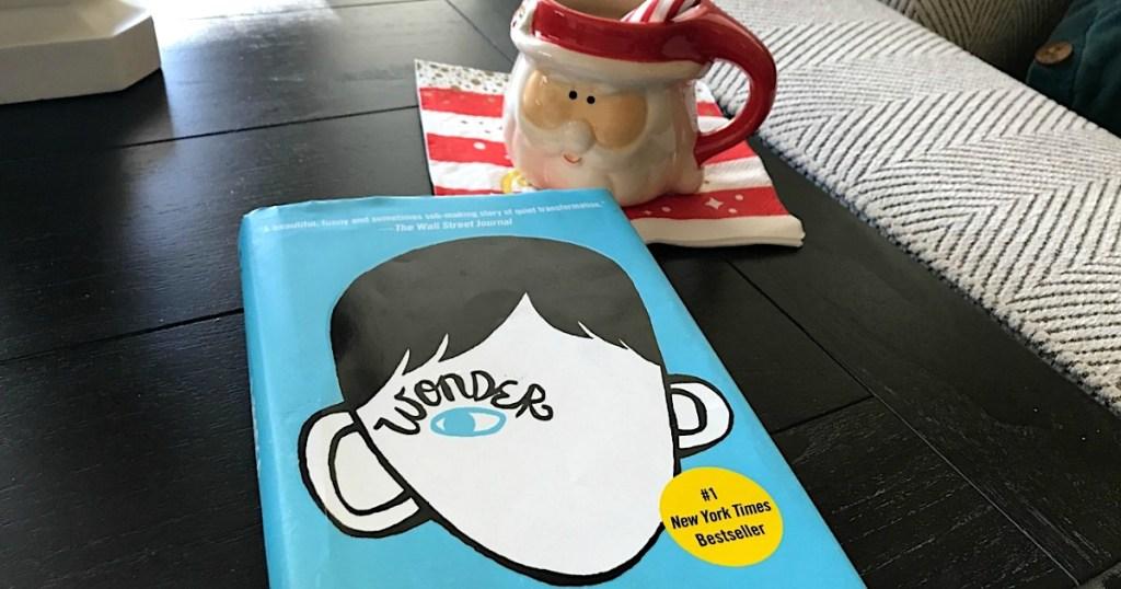 Wonder hardcover book sitting on table by santa coffee mug