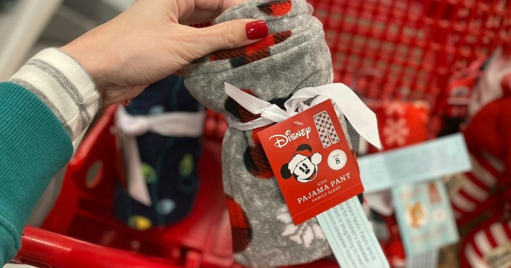 hand holding MIckey Mouse pants by shopping cart