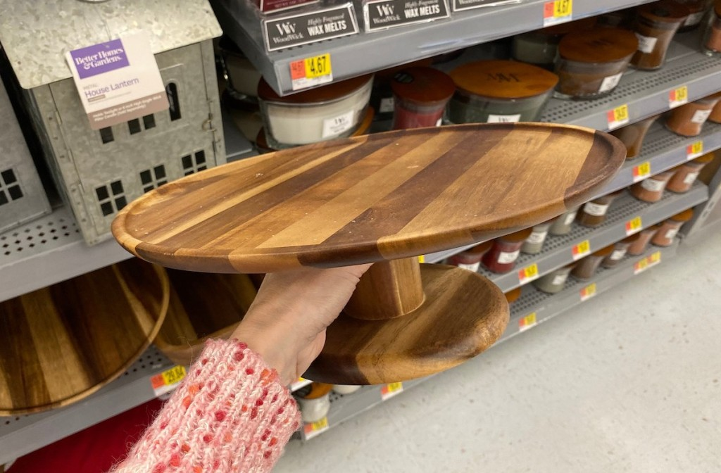 hand holding wooden cake stand in store