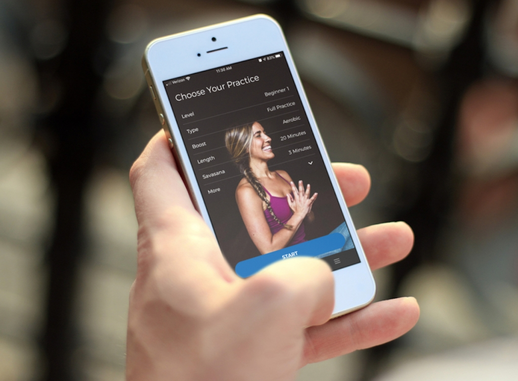 hand holding a phone with yoga app on screen
