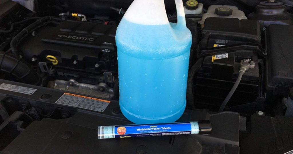 gallon of windshield cleaner and tube of tablets sitting on car parts under car hood