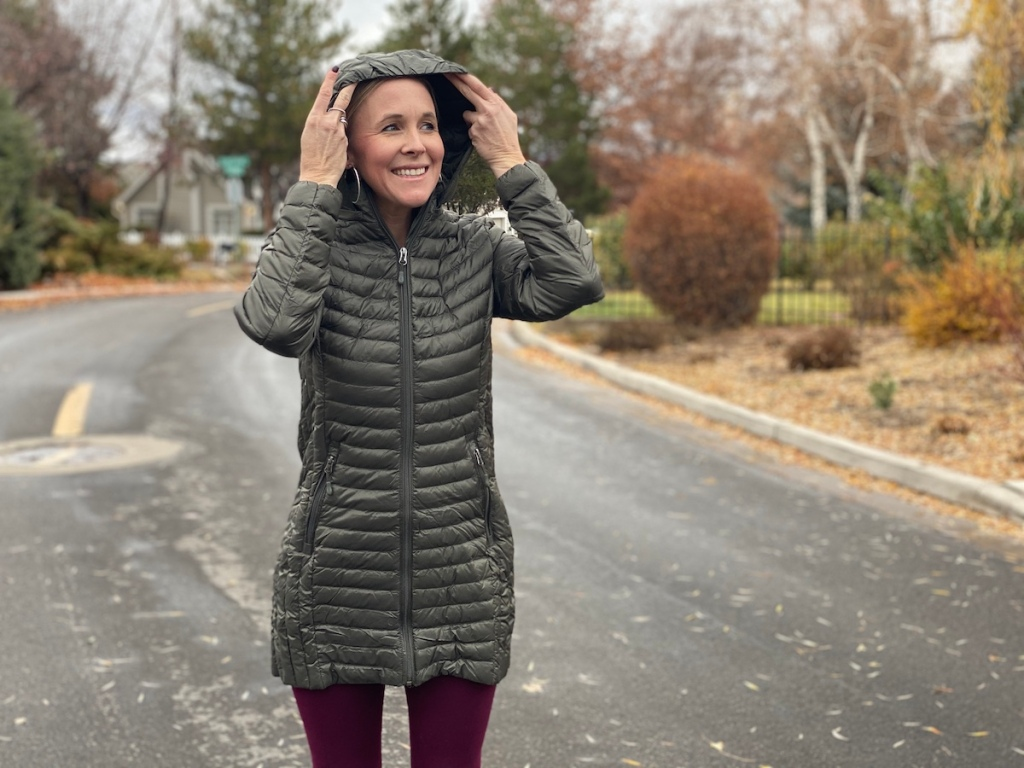 woman putting hood up on puffer jacket