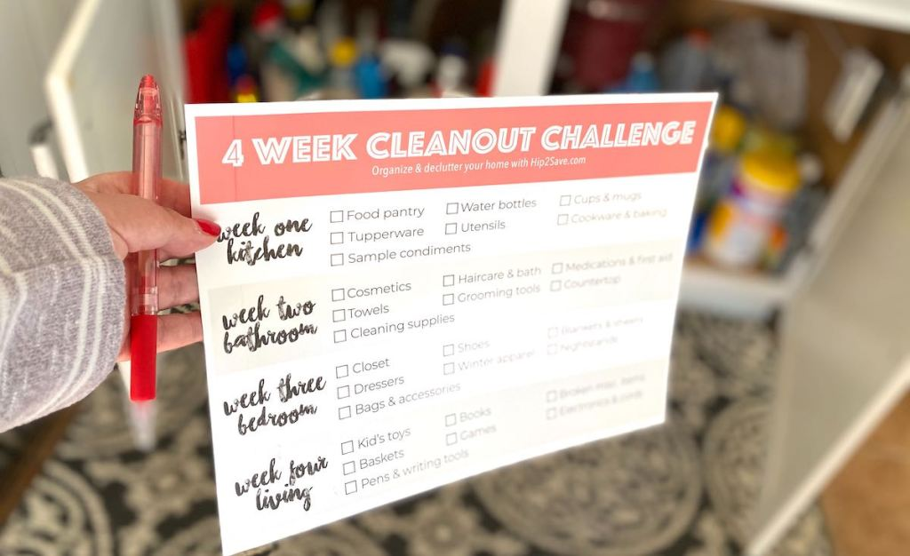 hand holding paper with 4 week declutter your home cleanout challenge checklist