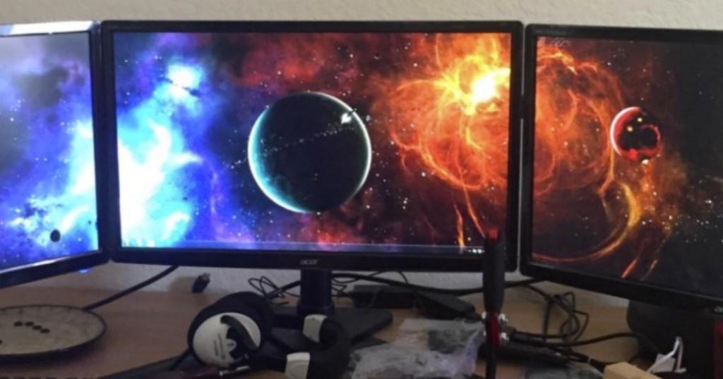 Three gaming monitors set up with vivid image of planets