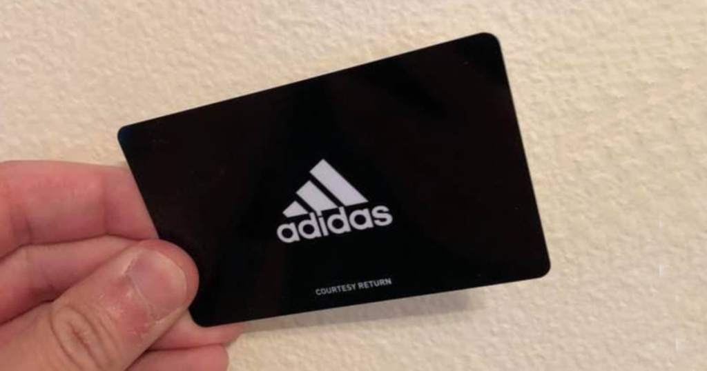 Hand holding adidas gift card