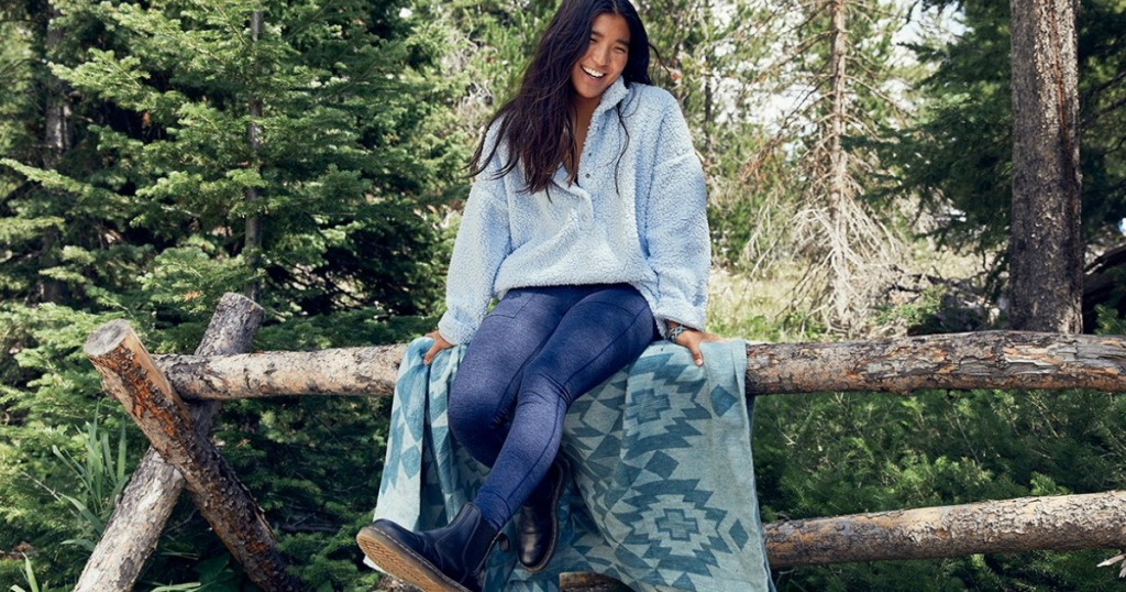 woman in blue leggings and sherpa top sitting on a log fence outside