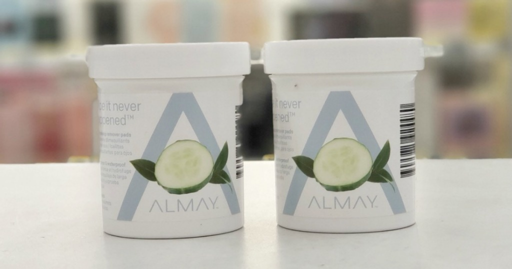 Two containers of Almay brand eye makeup remover pads on counter in store