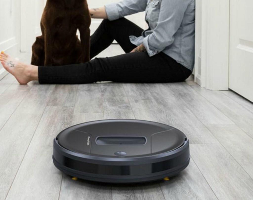 Black circular robotic vacuum on hardwood floor