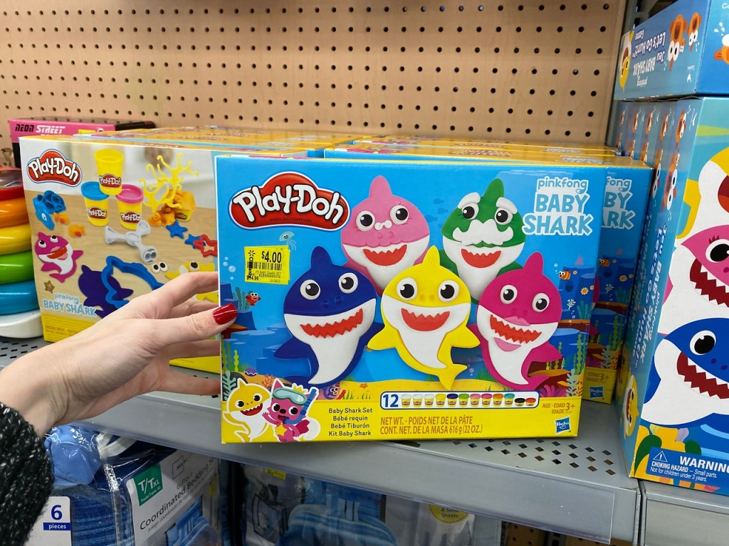 Baby Shark Play Doh Set on store shelf with woman's hand turning it