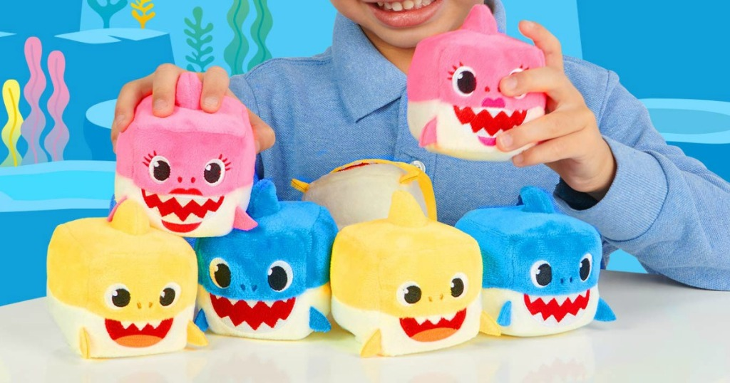 Young boy playing with Baby Shark plush cubes