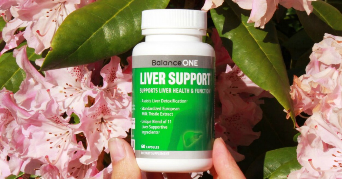 someone holding Balance One Liver support capsules in front of flowers