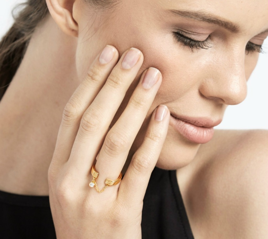 woman wearing a gold initial ring and holding her hand up to her face