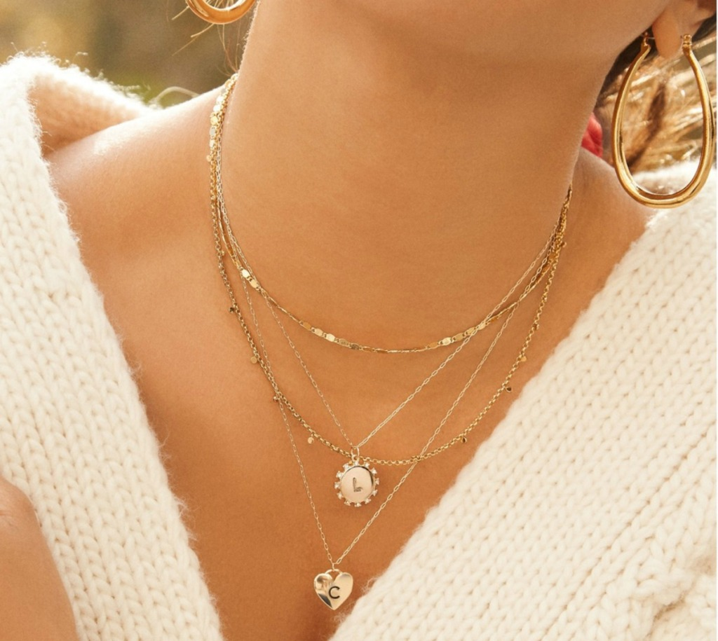 woman in white sweater wearing multiple gold initial pendant necklaces