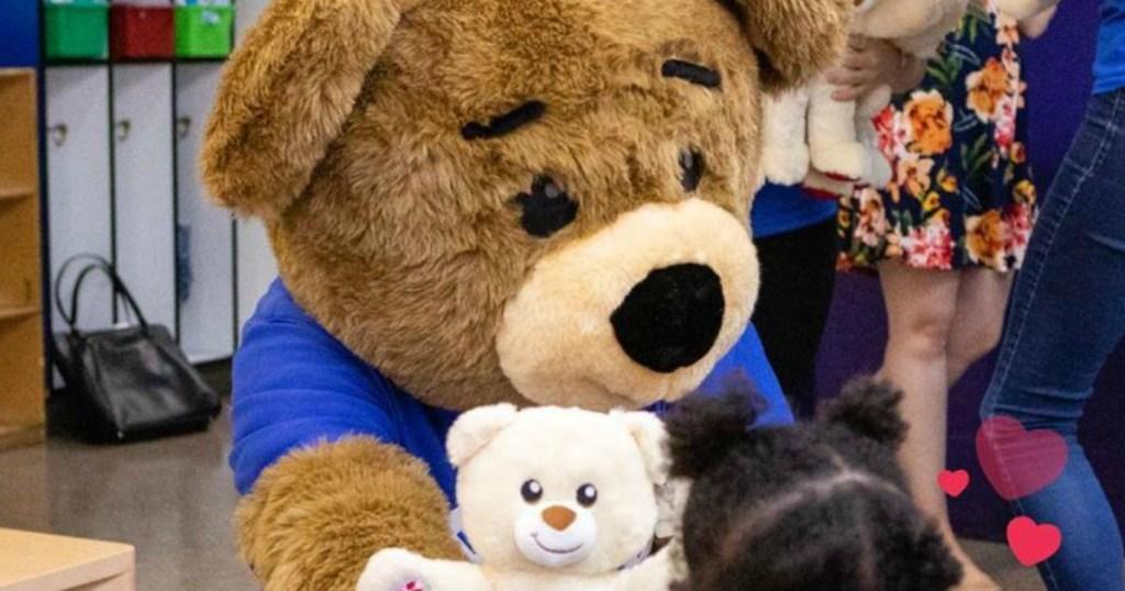 Bearemy Build-A-Bear mascot giving a small bear to a little girl