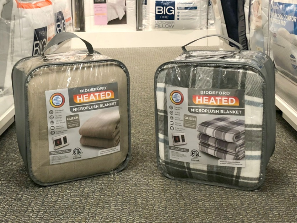 Two packages of heated blankets on floor in Kohl's