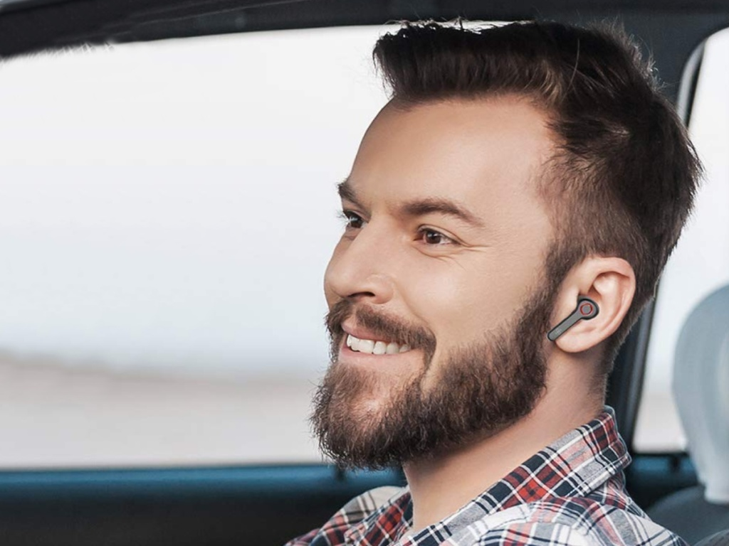 Man sitting in a car wearing Boltine Wireless Earbuds