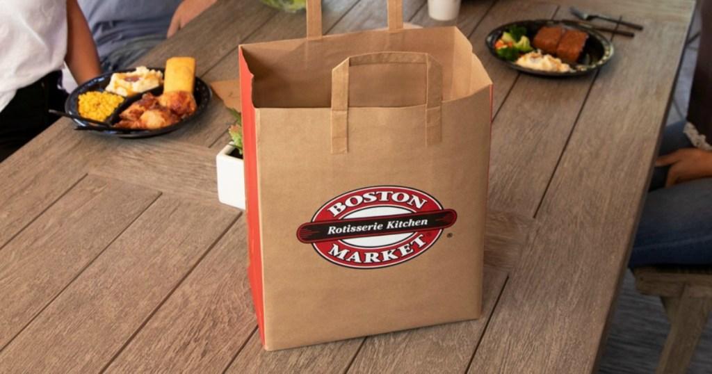Boston Market bag of food at table