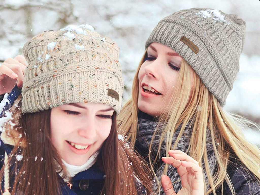 Two women in the snow wearing knit beanie hats