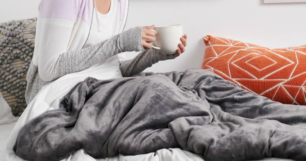 Woman holding white coffee mug tucked in with a gray weighted blanket