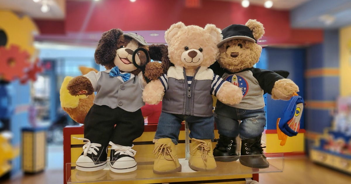 Three Build-A-Bear stuffed animals in outfits on display at store entrance