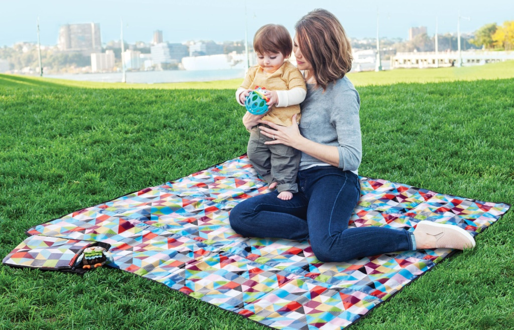 baby and mom sitting on Central Park Outdoor Blanket & Cooler Bag in park