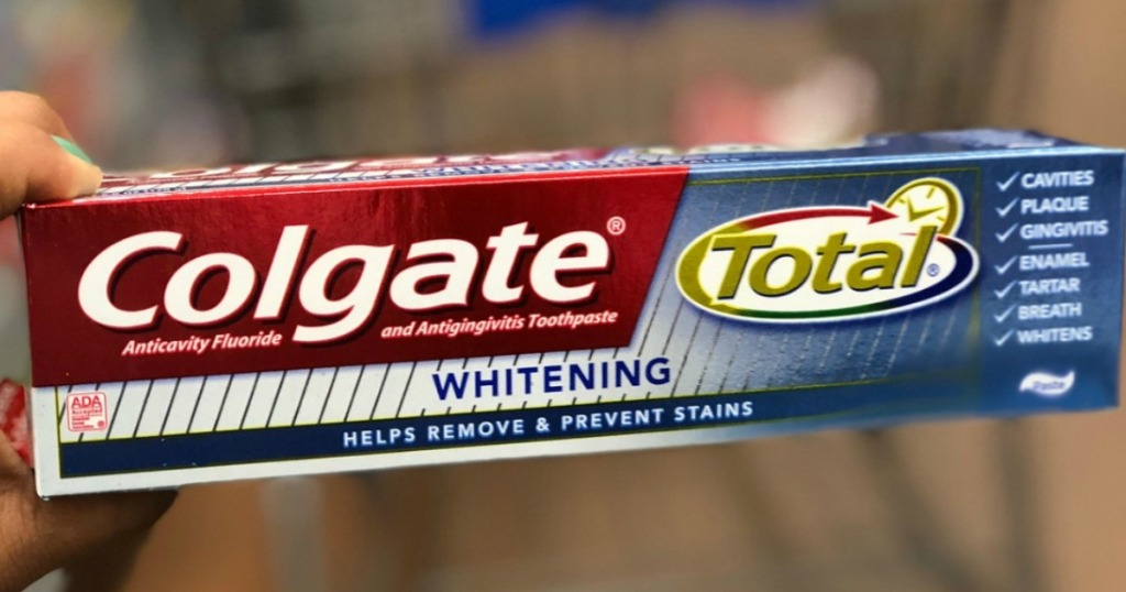 hand holding Colgate Toothpaste Whitening