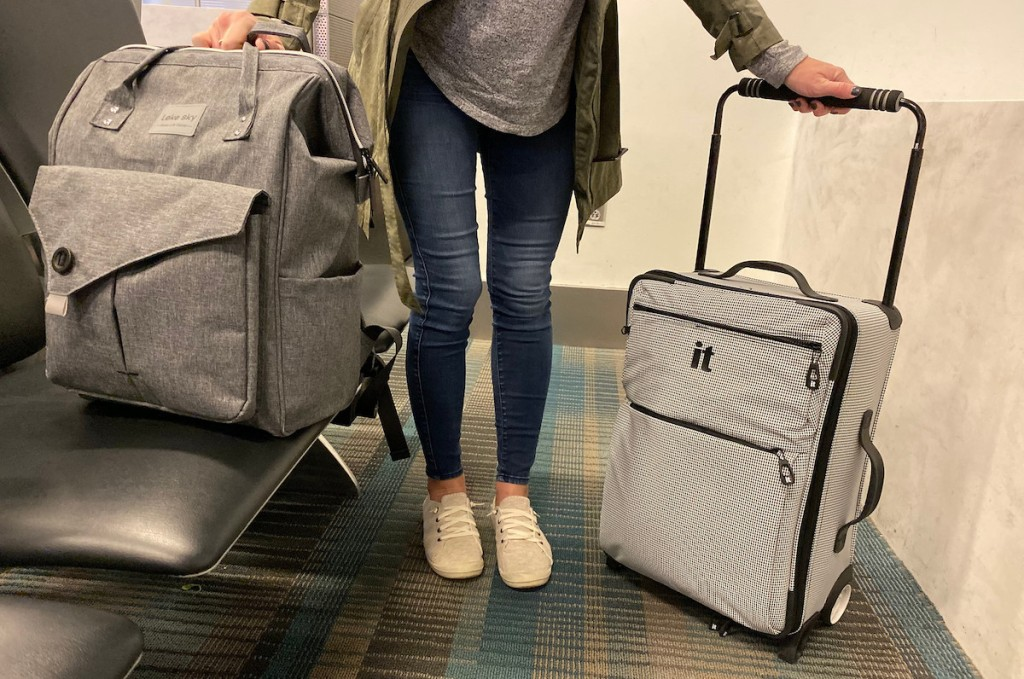 person in airport holding gray bookbag and carry on sized luggage