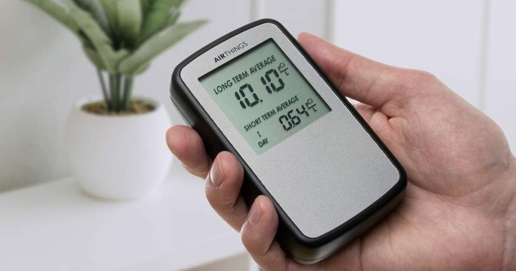 Hand holding Corentium Home Radon Detector by Airthings