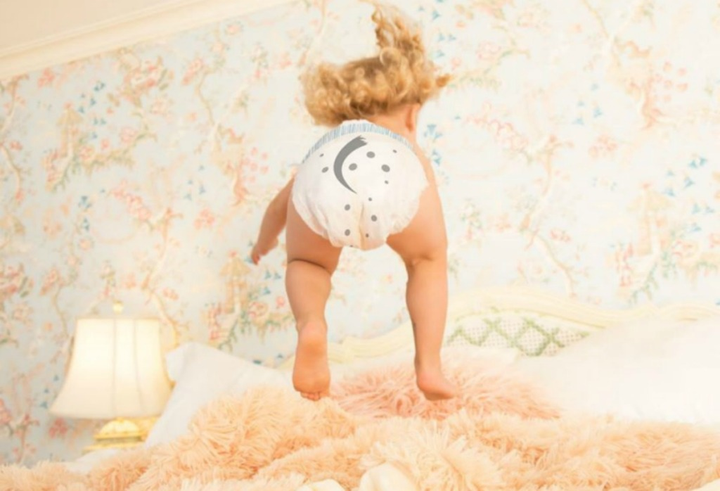 toddler in a diaper jumping on a bed