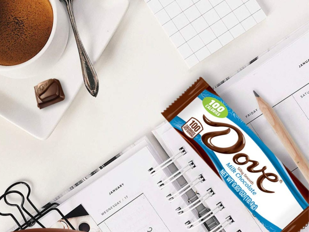 dove candy bar resting on calendar book with coffee and a piece of dove chocolate next to it