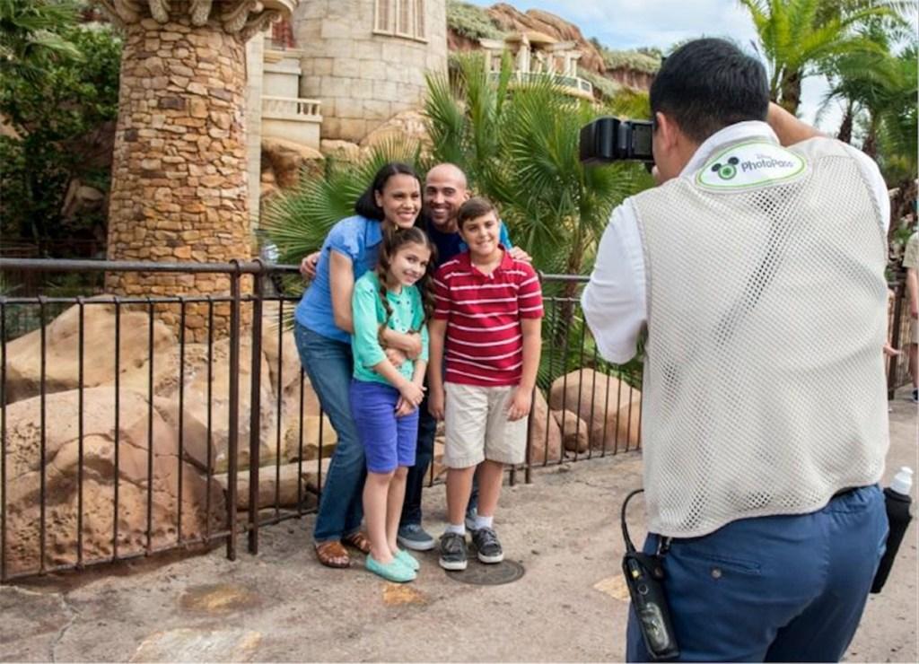 family getting their photo taken by Disney employee at Disney World