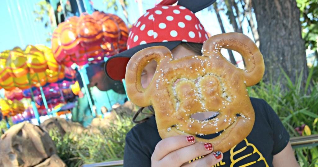 girl holding Mickey pretzel at Disneyland