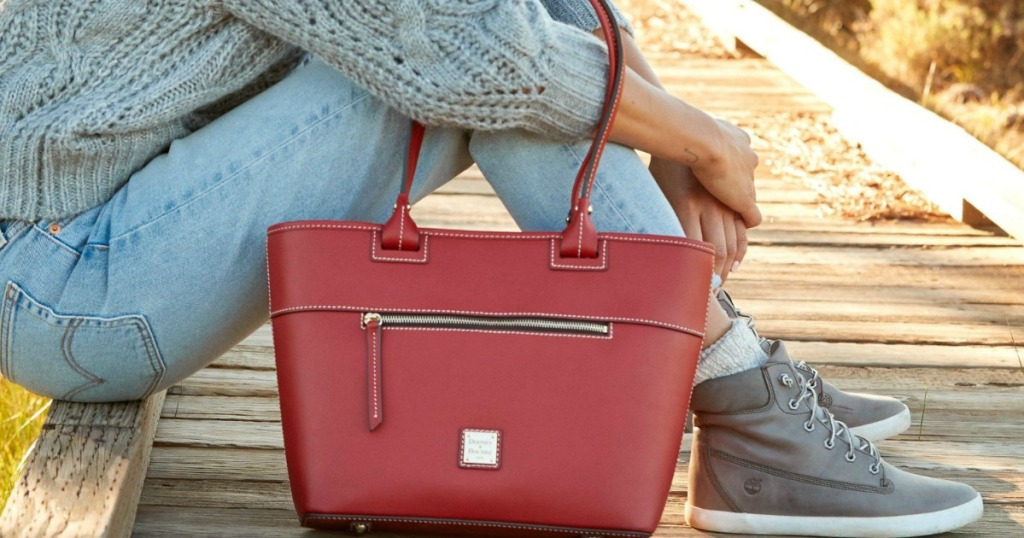 Woman sitting on boardwalk with red leather tote bag