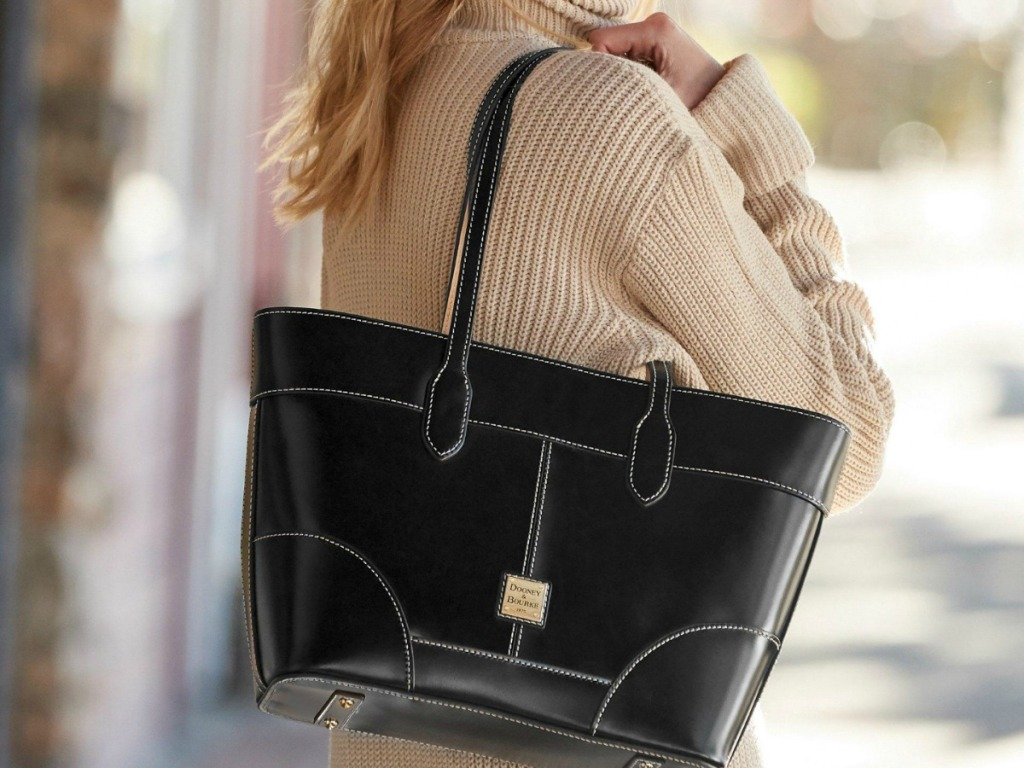 Woman wearing sweater and black luxury brand leather tote bag