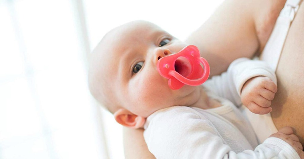 woman holding a baby sucking on a pacifier
